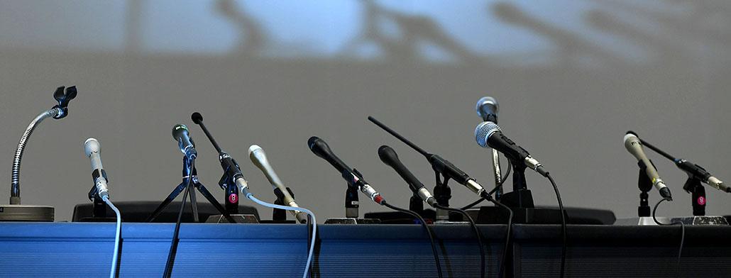 pressroom met foto van een tafel met microfoons