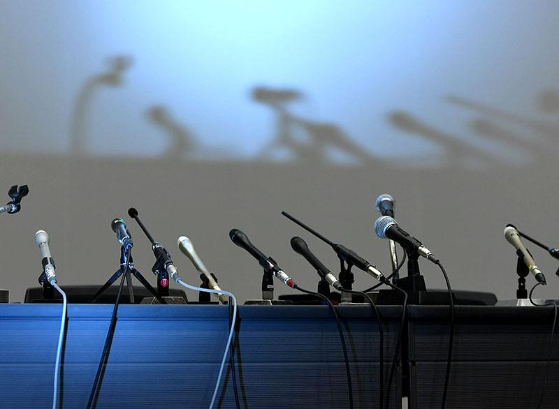 Home foto van tafel met microfoons bij een persconferentie